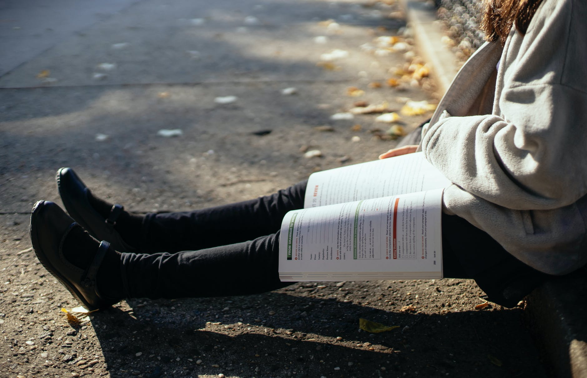 crop faceless student with textbook sitting on ground in park